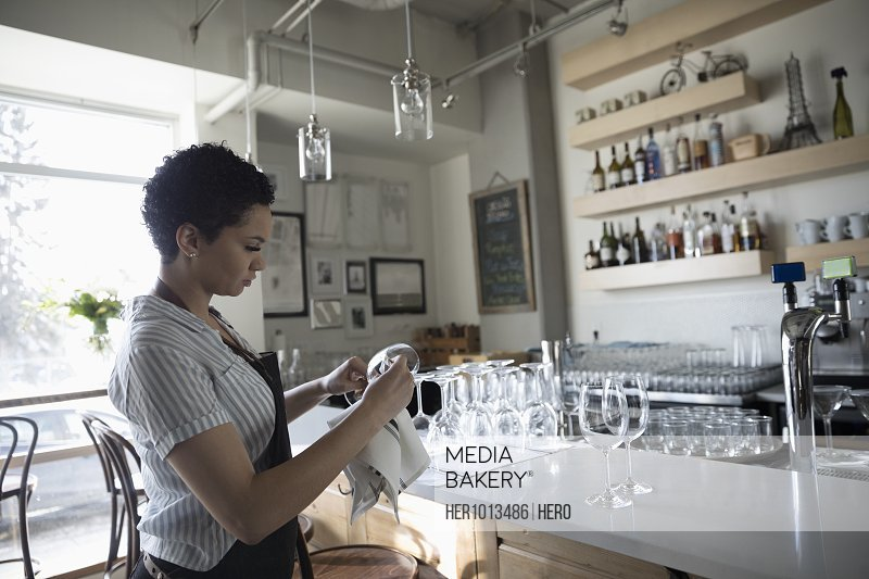 Young woman small business owner drying wine glasses in bar