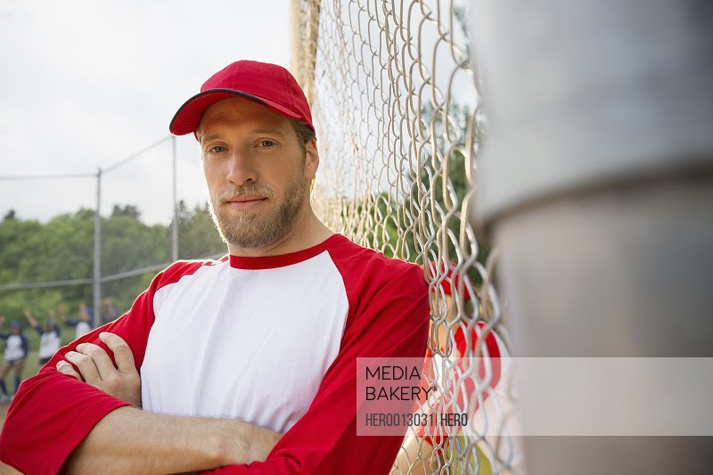 Baseball player leaning on chain link fence