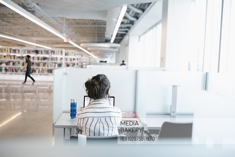 Student in study booth using laptop in university library
