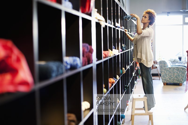 restocking shelves at yarn store