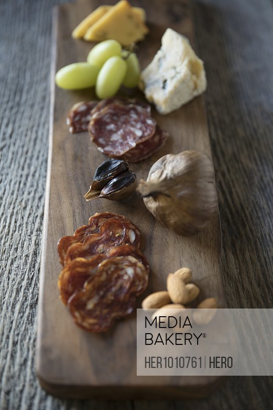Close up still life charcuterie featuring cheese, salmi, nuts and fruit on rustic wooden board