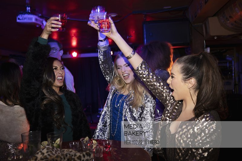 Exuberant young women friends toasting cocktails in nightclub