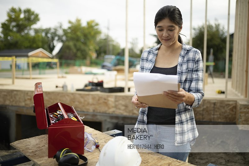 Woman with clipboard working at construction site