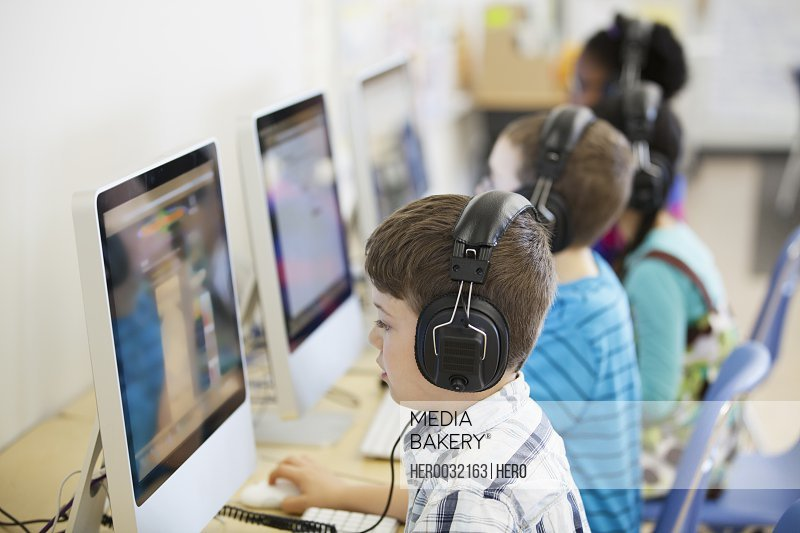 elementary students with headphones in computer lab