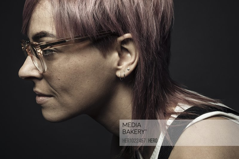 Profile portrait beautiful non-binary gender person with pink hair and eyeglasses