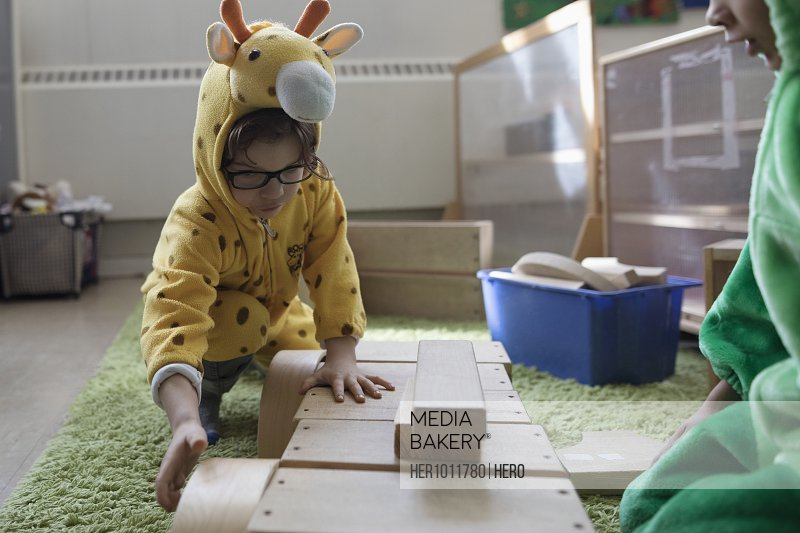 Preschool boy in giraffe costume playing with wood blocks in classroom