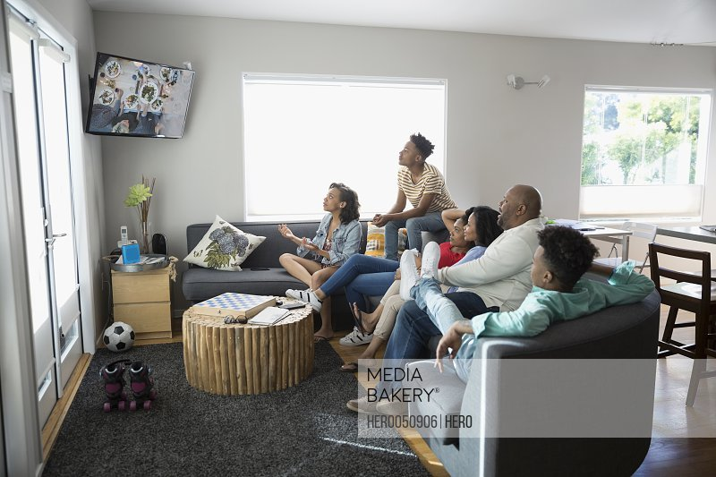 Photo by Hero Images - African American family watching TV in living room