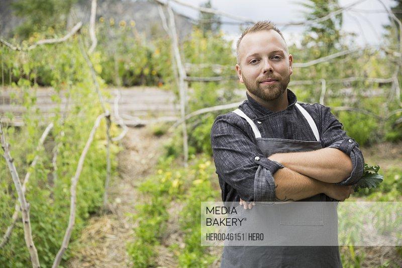 Portrait confident farm-to-table chef in vegetable garden