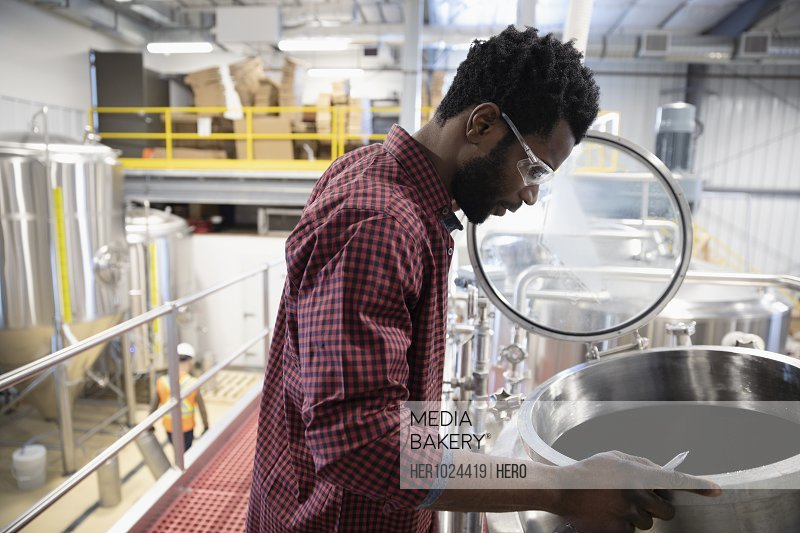 Male brewer examining beer in fermentation tank in brewhouse distillery