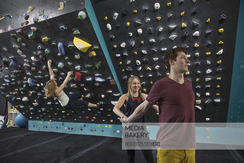 Rock climbers helping each other stretch, preparing at climbing gym
