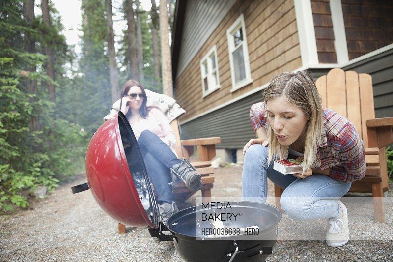 Woman preparing barbecue outside cabin