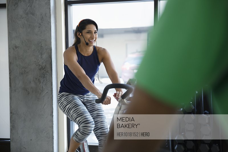 Instructor on exercise bike leading spin class in gym