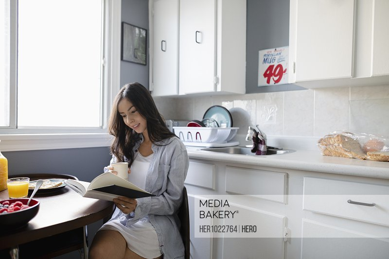 Young Latinx woman drinking coffee and reading book in morning kitchen