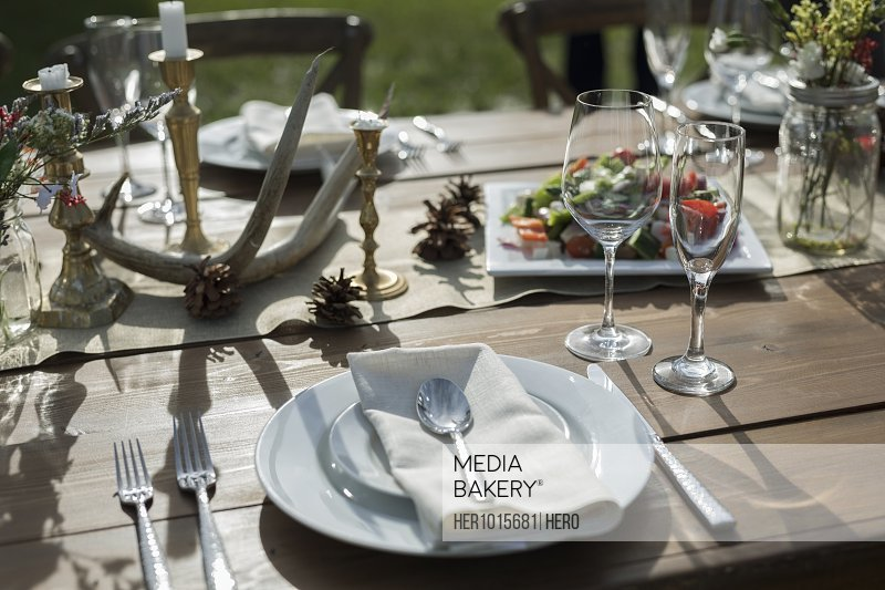 Flowers, food and placesettings on sunny patio table