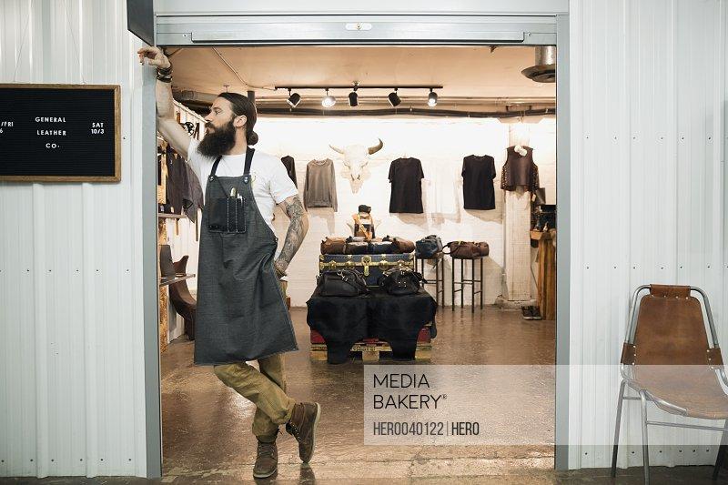 Leather shop owner entrepreneur leaning in doorway