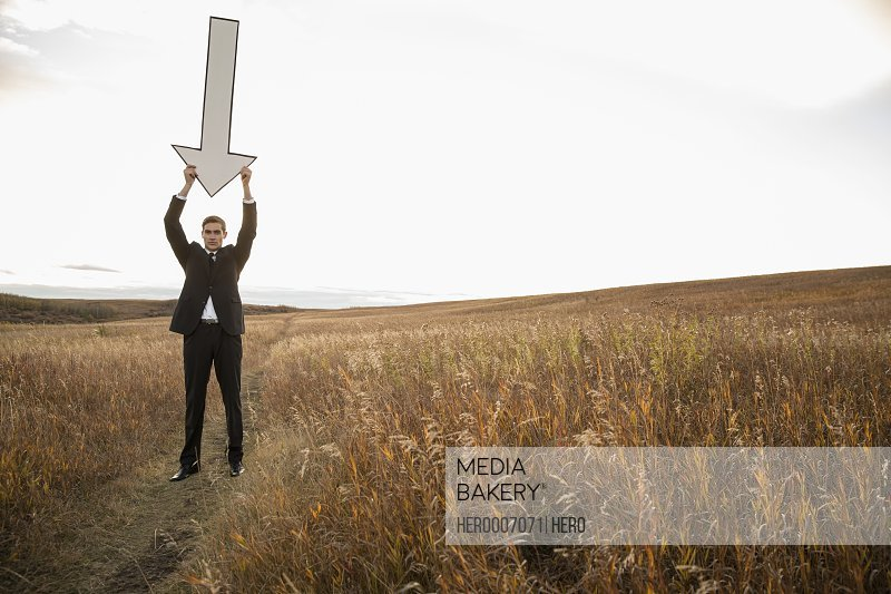 Businessman holding large arrow