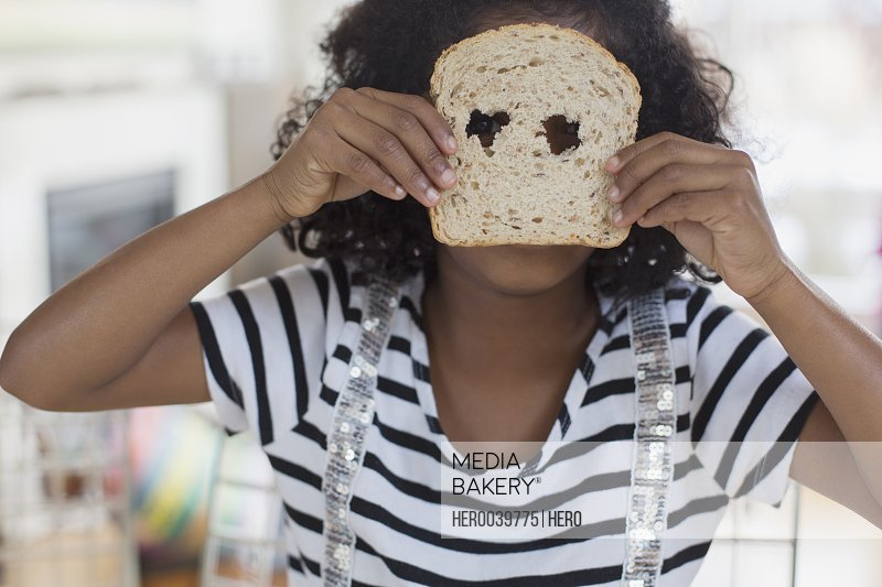 Little girl with mask made from bread slice