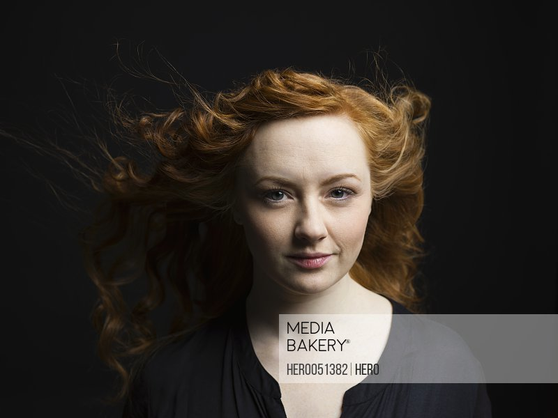 Portrait woman with wind blowing long curly red hair against black background