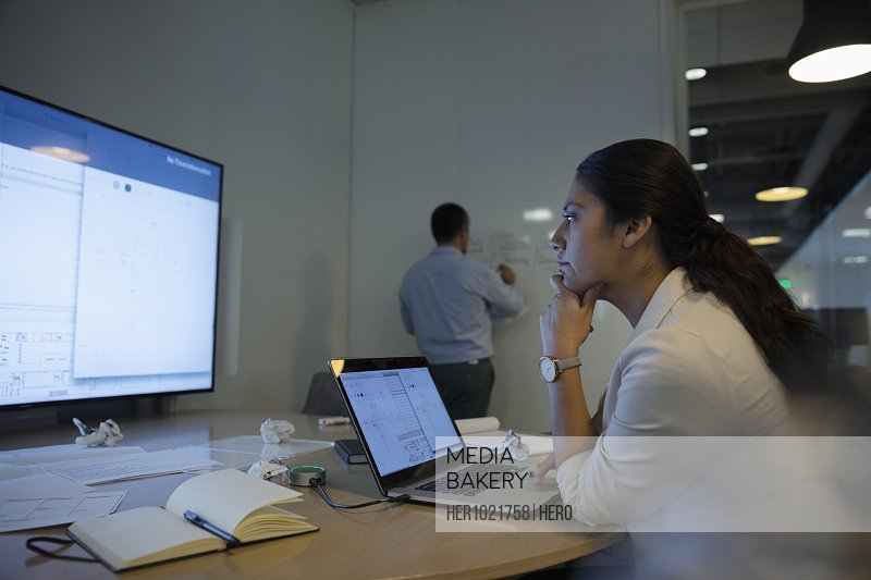 Focused businesswoman using laptop in conference room meeting