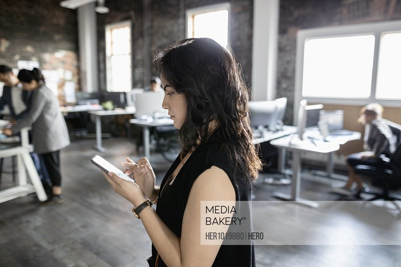 Creative businesswoman using smart phone in loft office