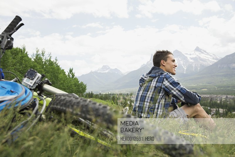 Man with mountain bike sitting in grass