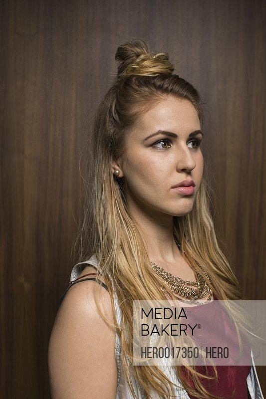 Pensive blonde woman with hair bun looking away