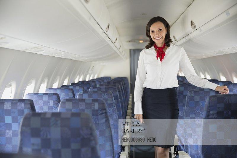 Portrait of flight attendant standing in airplane cabin