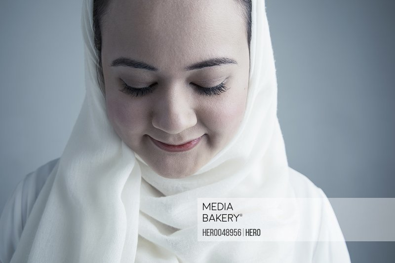 Close up portrait smiling Middle Eastern young woman in white hijab looking down