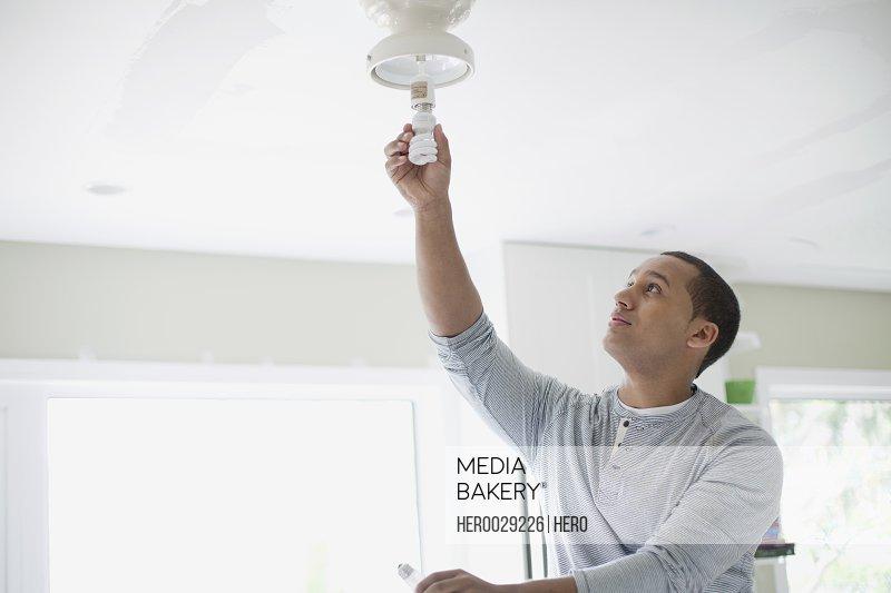young adult latino man replacing light bulb