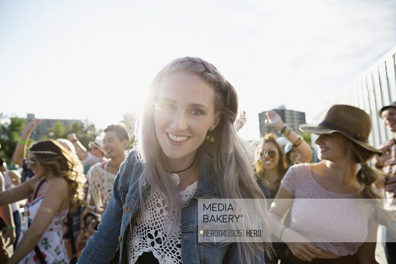 Portrait smiling young woman at summer music festival