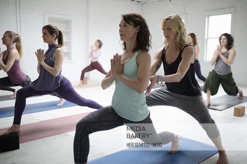Yoga instructor guiding woman practicing warrior one pose