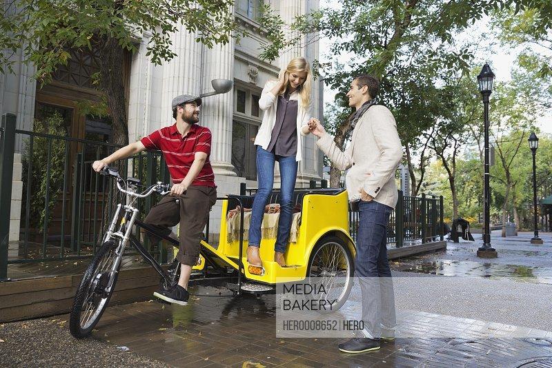 Man assisting woman out of rickshaw