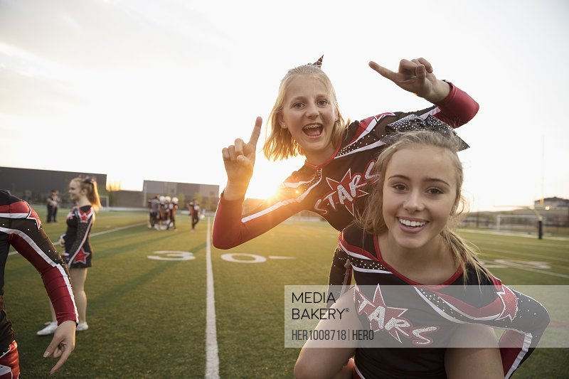 Portrait enthusiastic teenage girl high school cheerleaders piggybacking and gesturing on sideline of football field
