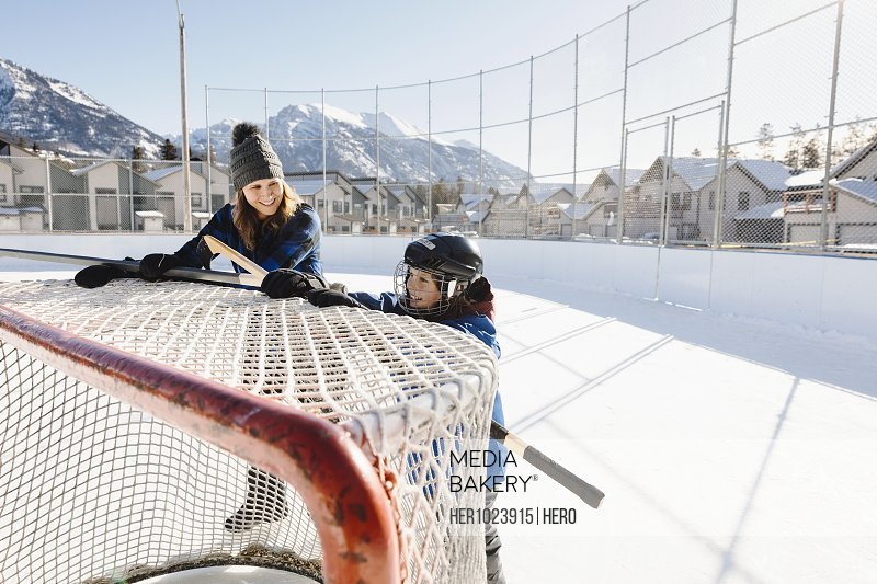 Mother and son pushing outdoor ice hockey goal