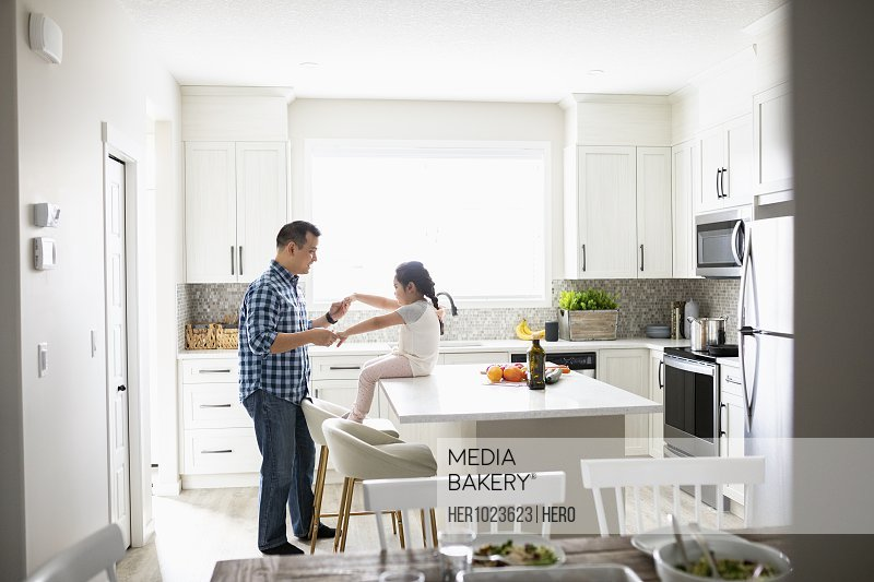 Playful father and daughter in kitchen
