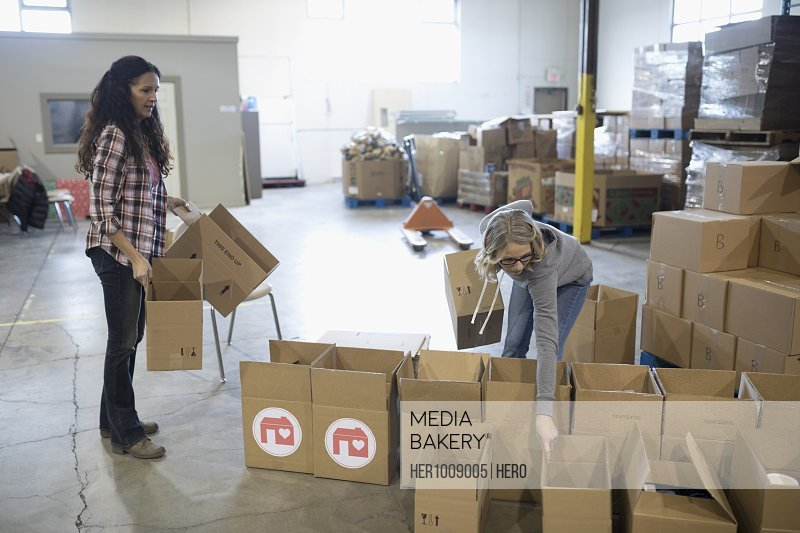Female volunteers preparing donation boxes in warehouse
