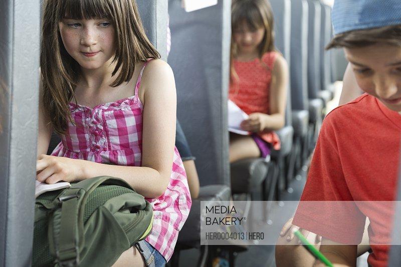 Cute girl looking at friend sitting inside school bus
