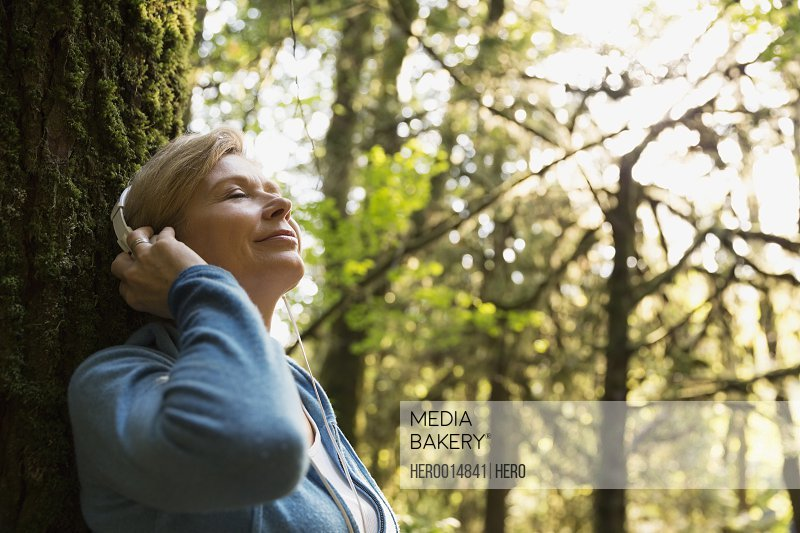 Serene woman listening to music in woods