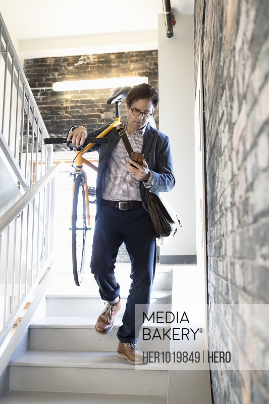 Businessman with smart phone carrying bicycle in stairwell