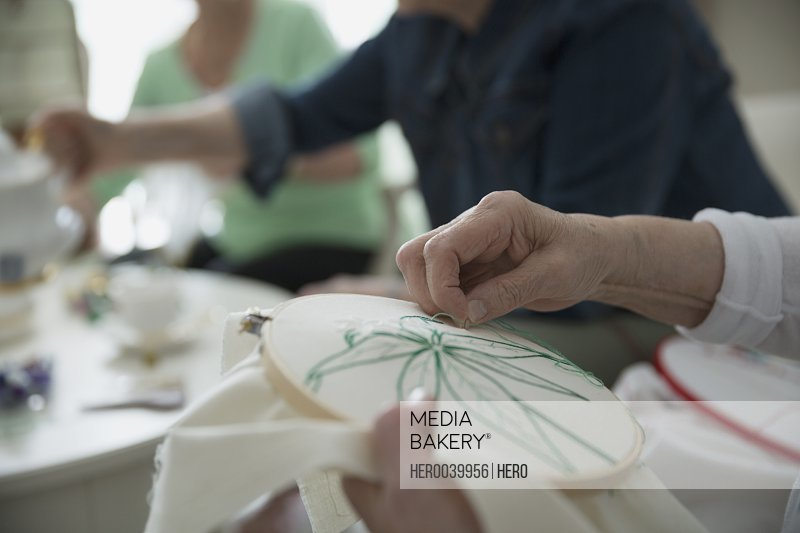 Close up senior woman embroidering flower