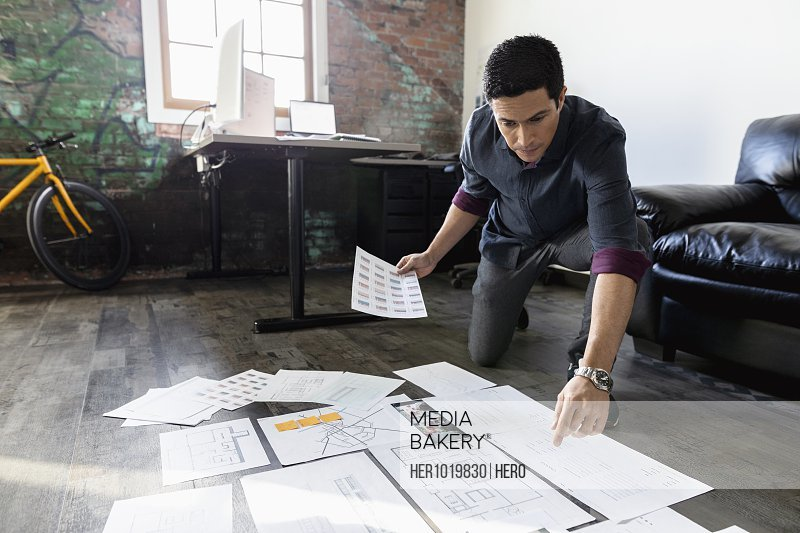 Creative businessman reviewing proofs on office floor