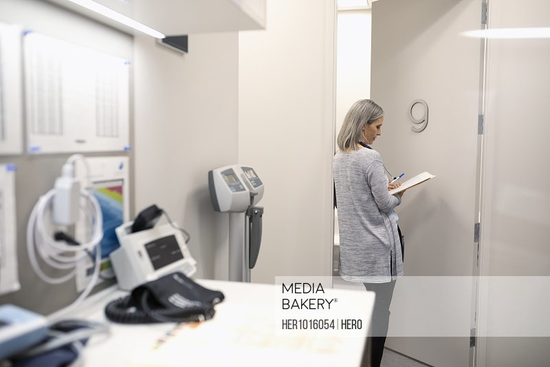 Female doctor reviewing medical record at clinic doorway