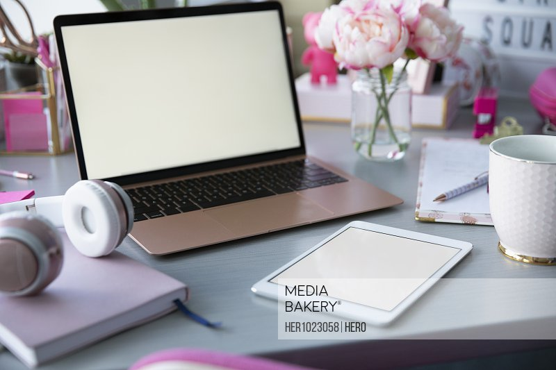 Pink peonies, laptop and office supplies on desk