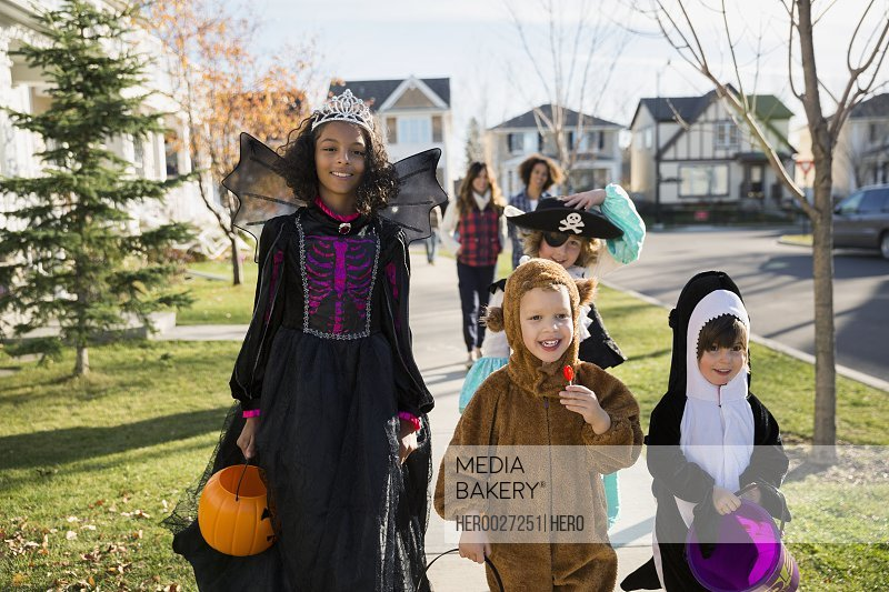 Kids in Halloween costumes on neighborhood sidewalk