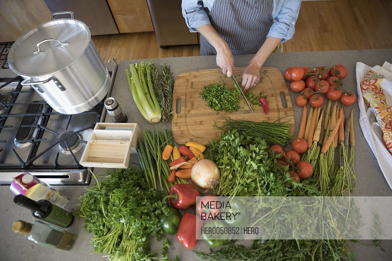Overhead view woman cutting vegetables in kitchen