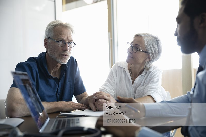 Medical consultant discussing medical insurance with senior couple