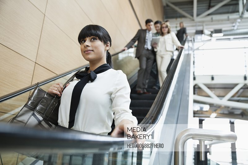 Businesswoman using escalator in office building