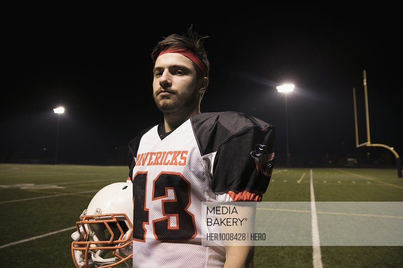 Portrait confident, tough teenage boy high school football player on football field at night