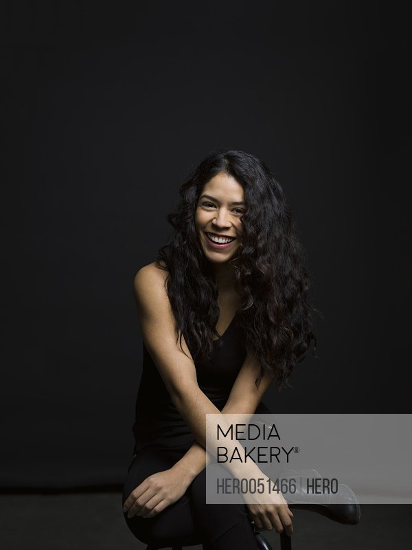 Portrait laughing Latina woman with long curly black hair against black background