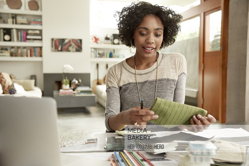 Female interior designer browsing fabric swatches at home office desk